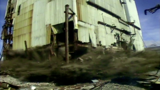 vidéos et rushes de ms cu sacrificial camera shot at base of mill building as it is demolished in controlled implosion using explosives /   for william, scotland, uk - imploding