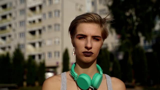 vidéos et rushes de adolescente triste et mélancolique marchant dans la rue - piercing