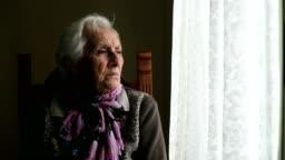 sad and pensive old woman sitting near the window
