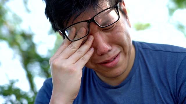 trauriger asiatischen mann schlechte nachrichten auf dem handy lesen - bedauern stock-videos und b-roll-filmmaterial