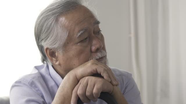 自宅で孤独を感じて歩く杖を持つ悲しいアジアの先輩男性。 - 老化点の映像素材/bロール