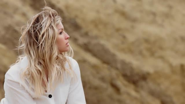 vídeos de stock e filmes b-roll de sad blond woman on a background of brown mountains - só mulheres jovens