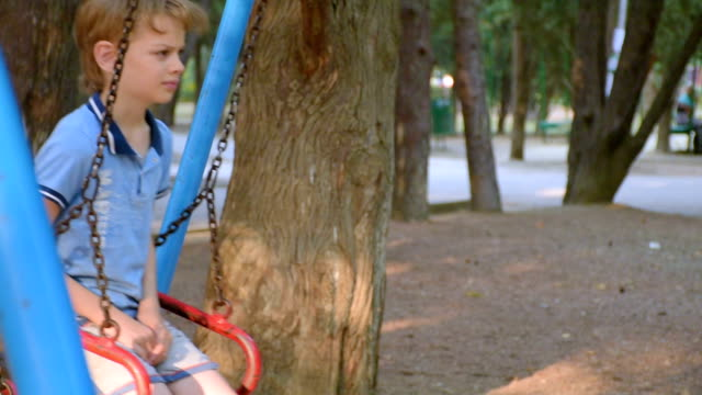 sad boy swinging on a swing in park