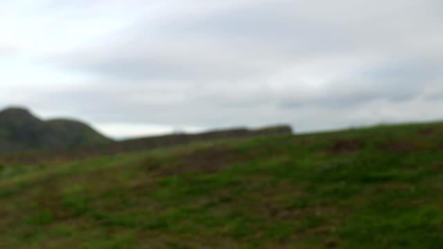ein trauriger junge mit der flagge schottlands vor der kulisse des arthur es seat berges - schottisches hochland stock-videos und b-roll-filmmaterial