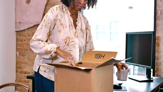 vídeos de stock, filmes e b-roll de triste empresária embala pertencimento após ser demitida durante a pandemia coronavírus - trabalhadora de colarinho branco