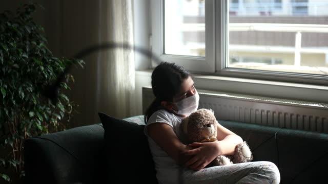 sad child in home quarantine at the window holding teddy bear. coronavirus covid-19 - teddy bear stock videos & royalty-free footage