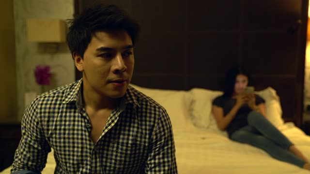 a sad couple not talking to each other after the quarrel. pensive upset man feeling offended, thinking over problems in relationships, anxious about future, upset woman sitting in the background. - deception stock videos and b-roll footage