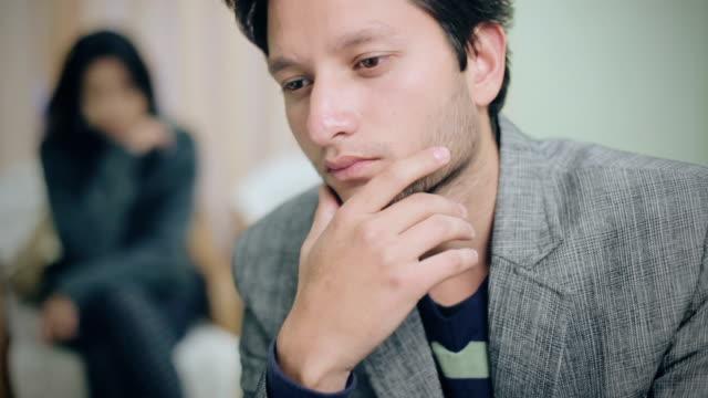 vídeos de stock e filmes b-roll de sad couple, selective focus is on young man. - law