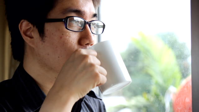 sad, depressed, anxious asian man drinking coffee by the window