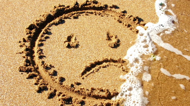 Sad face drawn in sand, washed away by sea.
