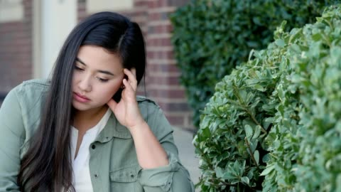 sad female college student sits alone on campus - confusion stock videos & royalty-free footage