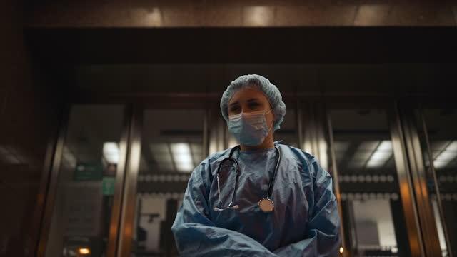 vídeos de stock e filmes b-roll de sad female nurse or doctor feeling down near hospital during night shift - bata cirúrgica
