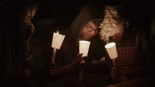 sad friends talking at candlelight vigil at night / provo, utah, united states - trauernder stock-videos und b-roll-filmmaterial