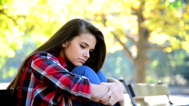 sad girl sitting on a bench - anxiety stock videos & royalty-free footage