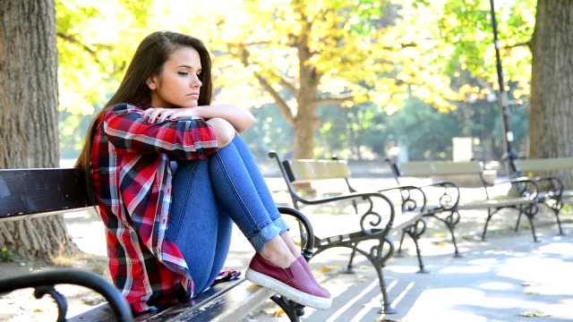 sad girl sitting on a bench - bench stock videos & royalty-free footage