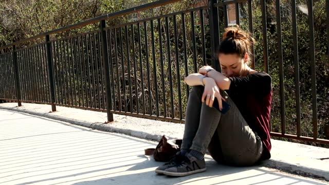 vídeos de stock, filmes e b-roll de menina triste sentado numa ponte - deteriorado