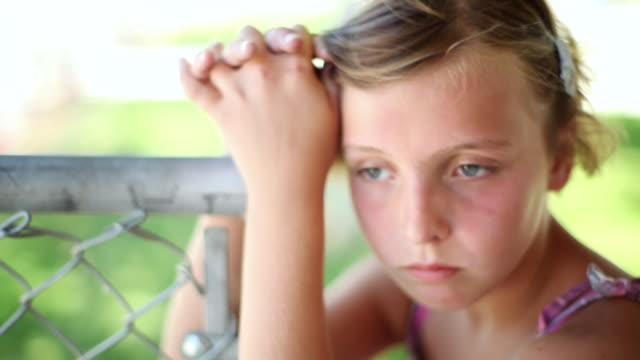 stockvideo's en b-roll-footage met cu sad little girl leaning on fencepost looking away / tracy, ca, united states - verdriet