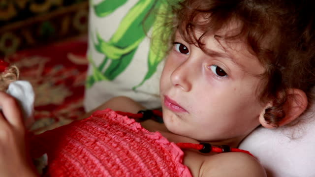 sad little girl lying in bed and rubbing her nose - rubbing stock videos & royalty-free footage