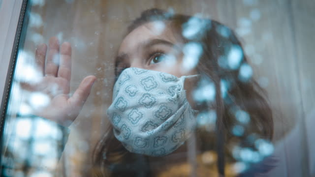 sad looking little girl with protective mask on her face looking through window because she is not allowed to go outside and play. - biohazard symbol stock videos & royalty-free footage