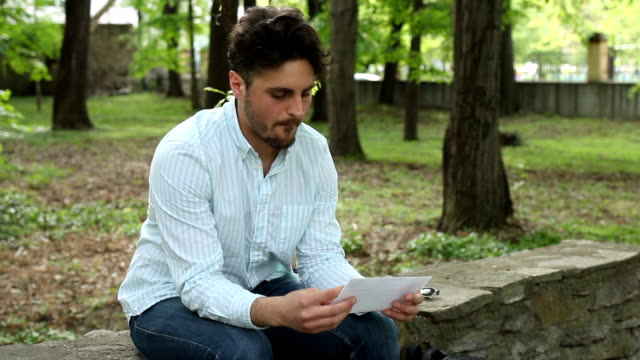 Sad looking male in the park, reading and tearing one letter.