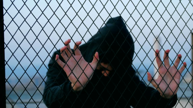a sad man behind fence - recinzione video stock e b–roll