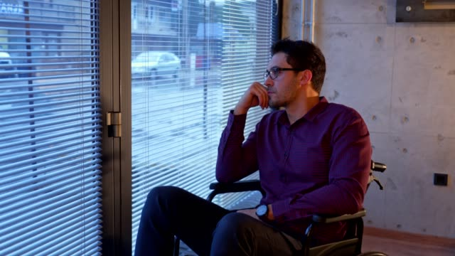vidéos et rushes de homme triste dans un fauteuil roulant, regardant par la fenêtre - chaise roulante