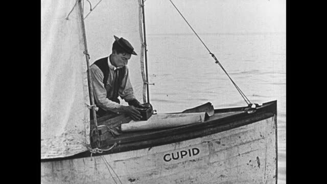 vídeos de stock, filmes e b-roll de 1923 sad man (buster keaton) sends tear-stained letter before setting off in his boat - 1923