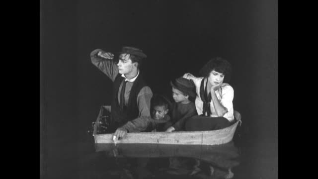 1921 Sad man (Buster Keaton) sits on boat as it sinks before swimming to family in lifeboat