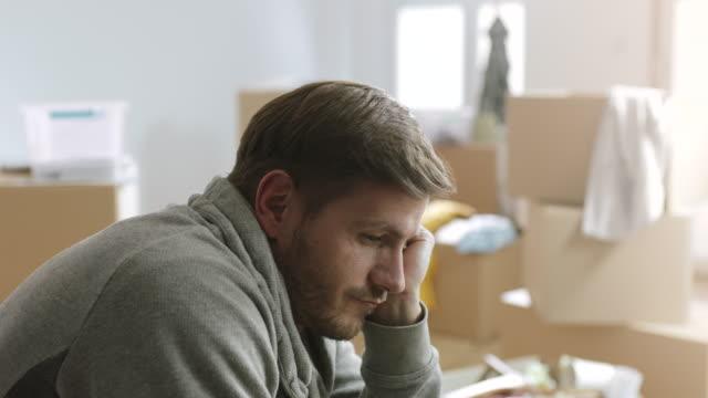 trauriger mann sitzt in seinem aparment voller kartons - erschöpfung stock-videos und b-roll-filmmaterial