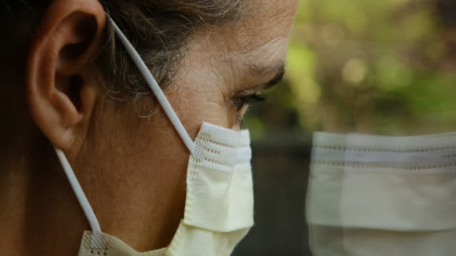 sad mature woman looking away through a window wearing a surgical mask - one mature woman only stock videos & royalty-free footage
