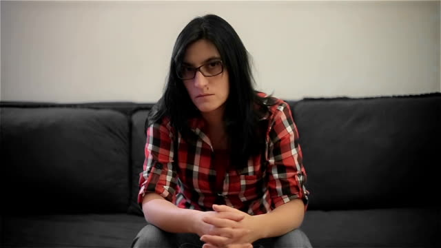 sad mature woman sitting on sofa and looking at the camera - tongue tied stock videos and b-roll footage