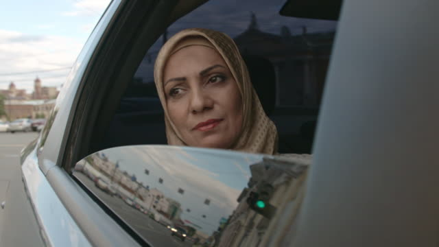 sad middle eastern woman riding in back seat - モデスト・ファッション点の映像素材/bロール