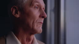 Sad old man crying near window, suffering loneliness, abandoned by relatives