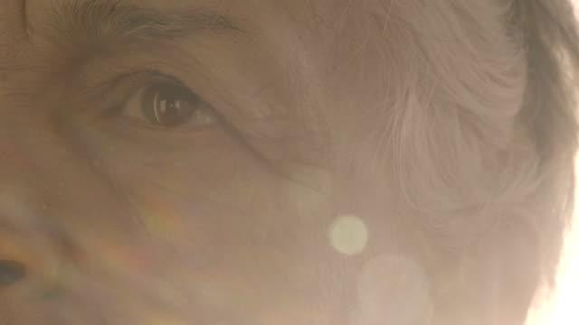 vidéos et rushes de gros plan d'yeux triste vieille femme - passé