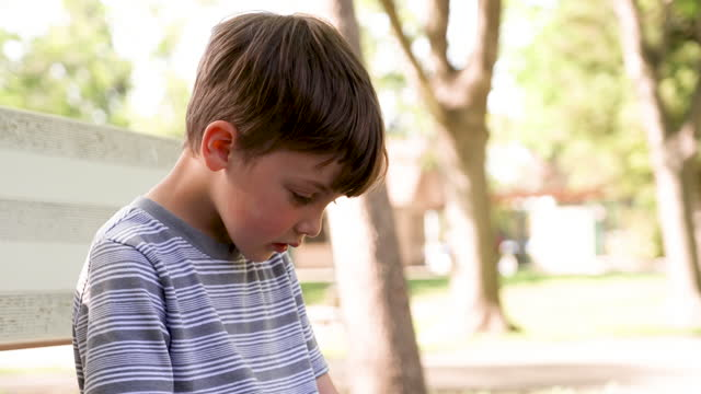 sad, pensive, little boy looking down sitting at the schoolyard suffering bulling - elementary age stock videos & royalty-free footage