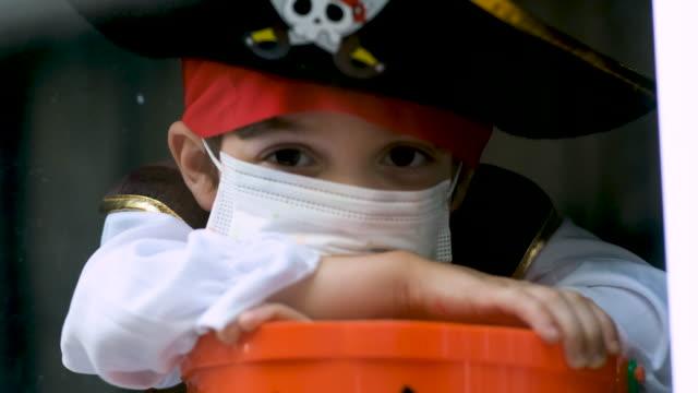 traurige nachdenkliche kleine junge trägt ein halloween-piraten-kostüm und eine schützende gesichtsmaske, die durch ein fenster mit einem jack o lantern eimer schaut - halloween stock-videos und b-roll-filmmaterial