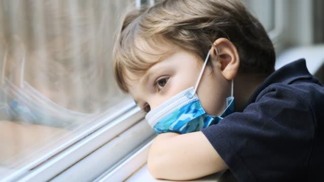 vídeos y material grabado en eventos de stock de triste niño pensativo que lleva una máscara protectora de la cara mirando a través de la ventana de su escuela - desesperación