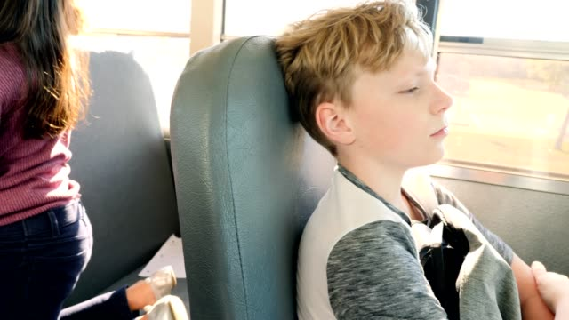 sad schoolboy riding on school bus - back to school stock videos & royalty-free footage