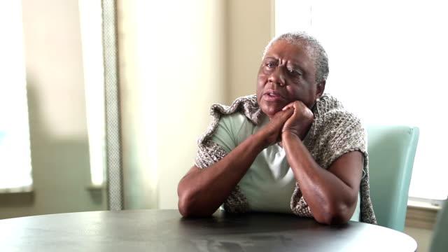 vídeos de stock e filmes b-roll de sad senior african-american woman sitting at home - inhaling