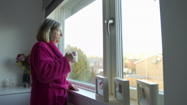 sad senior woman looking out of the window - stay at home order stock videos & royalty-free footage