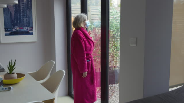 sad senior woman looking out of the window - bathrobe stock videos & royalty-free footage