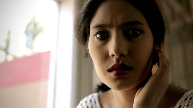 Sad, serene young woman thinking near window.