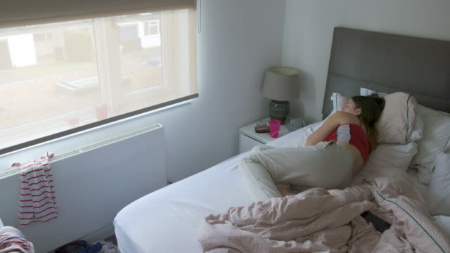 sad teenage girl on bed. she looks out of the window - teenagers only stock videos & royalty-free footage