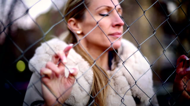 sad woman deeply rethinking her life. - chainlink fence stock videos and b-roll footage