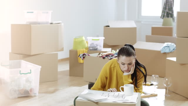 Sad woman looking apartment plans sitting on the floor