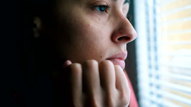 sad woman looking through window - tristezza video stock e b–roll