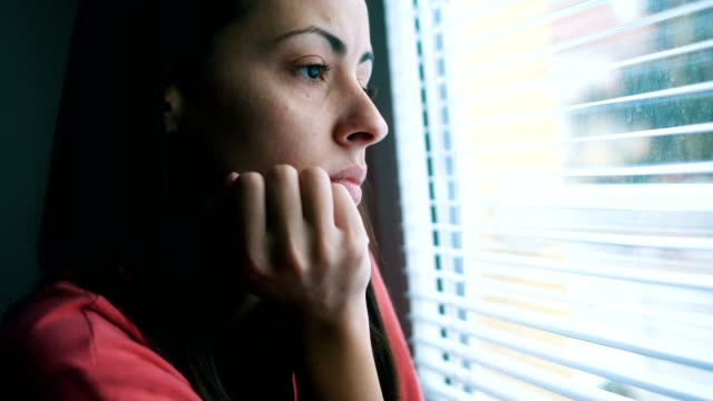 Sad woman looking through window