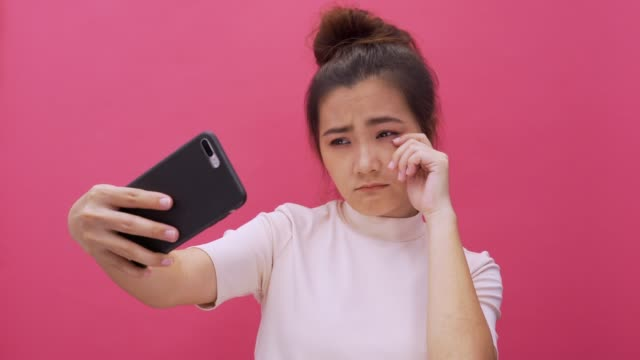 sad woman making selfie on smartphone on isolated pink background 4k - fake stock videos & royalty-free footage