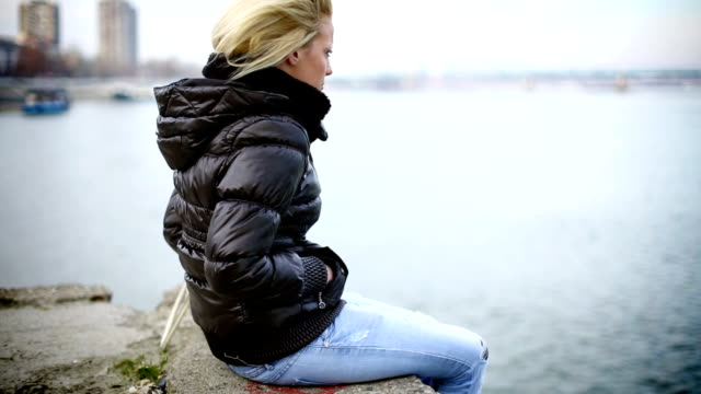 Sad woman sitting by the river.