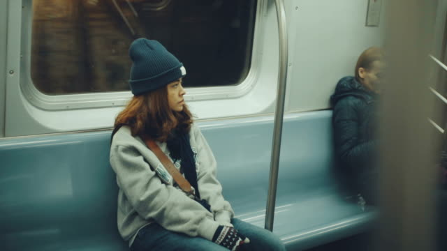 sad woman sitting in the subway - stazione della metropolitana video stock e b–roll